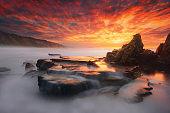 rock in Azkorri beach at sunset