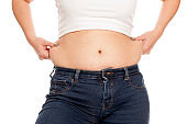 woman pinches her fat on her waist