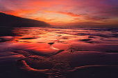 red sunset with puddles on beach shore