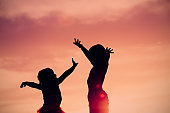 little boy and girl silhouettes play at sunset sky