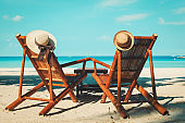 hats on chairs of tropical sand beach