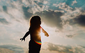 silhouette of happy little girl play at sunset