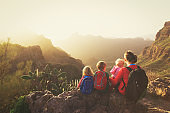 mother with three kids hiking in mountains