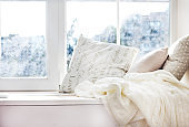 cushions and a knitted plaid on the windowsill.