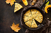 Pumpkin scones on a rusty stone or slate background, top view with copy space.