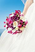 Bride hand holding flower bouquet on blue sky background