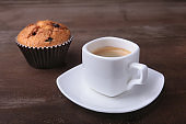 Homemade muffin with raisins and cup classic espresso coffee. selective focus.