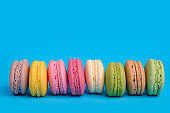 French macaroon cookies on light blue isolated background