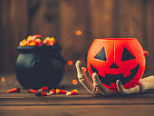 Halloween background with cauldron, candy and Jack O' lantern