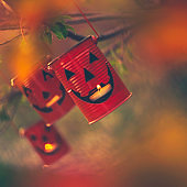 Jack O'Lanterns with candles hanging on tree branches