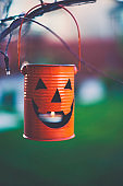 Jack O'Lantern with candle hanging on tree branches