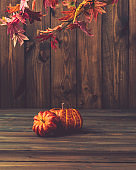 Fall background with pumpkins and leaves on wooden table