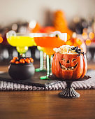 Halloween time. Vibrant drinks with Jack O'Lantern and candy