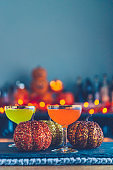 Halloween time. Vibrant cocktails with glittery pumpkins