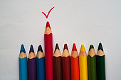 Wooden colorful crayons pencils red tick on white background