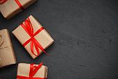 Three gifts in craft paper with red ribbon and bow on black background