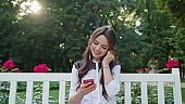 Lady in the Park Listening to Music on the Phone
