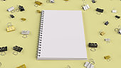 Blank spiral notebook with black, white and yellow binder clips on yellow table