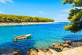 Fishing boat on blue sea in bay with beach in Primosten town, Dalmatia, Croatia