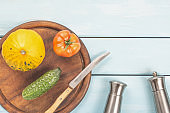 Salad delicatessen preparation. Vegetarian healthy food. Tomato, cucumber and bush pumpkin on cutting board with knife, saltcellar, pepper shaker on blue wooden background.