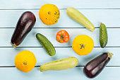 Vegetarian healthy food with vegetables. Tomato, cucumbers, bush pumpkins, eggplantsand marrows on blue wooden table.