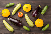 Vegetarian healthy food with vegetables. Tomato, cucumbers, bush pumpkins, eggplants nd marrows on dark wooden table.