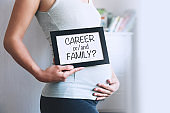 Pregnant woman holds whiteboard with text message - Career or/and Family?