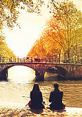 Couple friends or lovers relaxing on embankment of canal and looks at the river and bridges of Amsterdam.