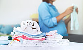 Pile of baby clothes, necessities and pregnant woman on bed in home interior of bedroom.
