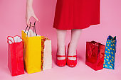 Colored bags for shopping are on a pink background. Red womens shoes and retro dress