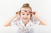 Funny little girl wearing eyeglasses imitates a strict teacher against white background.  Little student holding books.  Looking at camera.  School concept.