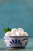 Mozzarella cheese with parsley branch on the wooden background