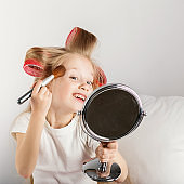 Fashion little girl making up with mirror.