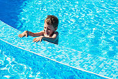 Happy kid playing in blue water of swimming pool. Little boy learning to swim. Summer vacations concept. Cute boy swimming in pool water. Child splashing and having fun in swimming pool