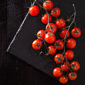 Small red cherry tomatoes on an old dark wooden table in rustic style