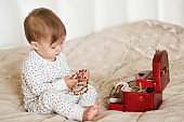 Baby girl playing with her mother's jewelry sitting on a bed in pajamas barefoot