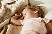 Carefree sleep little baby with a soft toy on the bed. Close-up portrait of a beautiful sleeping child on knitted blanket. Sweet dreams