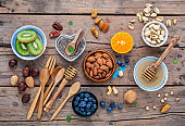 Ingredients for a healthy foods background, nuts, honey, berries, fruits, blueberry, orange, almonds, walnuts and chia seeds .The concept of healthy food set up on shabby wooden background. Flat lay.