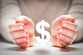 Dollar sign between woman's hands in gesture of protection. Currency stability