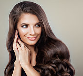 Glamorous Brunette Woman with Perfect Hairstyle and Makeup. Beautiful Model with  Long Healthy Hair Smiling