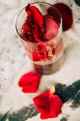 glass delicious refreshing drink of rose petal flower on blue wooden background, infusioned water