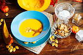 Pumpkin soup puree with spices on a wooden table