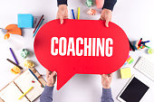 Two people holding speech bubble with COACHING concept