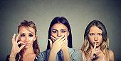 Keep a secret be quiet concept. Three secretive women keeping mouth shut.