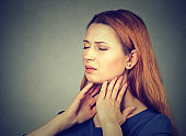 girl with sore throat touching her neck. Sick young woman having pain in her throat