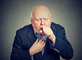Old man coughing holding fist to mouth isolated on gray background