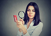 Curious business woman looking at credit card through magnifying glass
