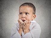 Closeup portrait nervous anxious stressed child boy biting fingernails