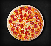 Pepperoni pizza on a black background.