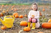 little girl farming on pumpkin patch
